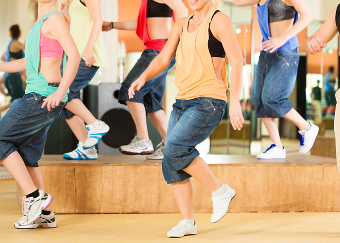 Zumba or Jazzdance - young people dancing in a studio or gym doing sports or practicing a dance number